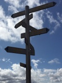 hiking sign post pointing to various cities around the world